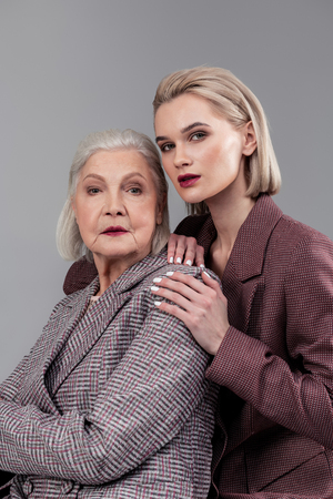 Wearing old-fashioned jackets. Short-haired luxurious women wearing office jackets and bold lipstick while posing for family photo