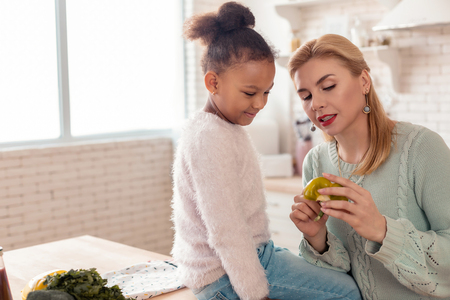 Healthy vegetables. Blonde-haired caring beautiful mother telling her daughter about healthy vegetables