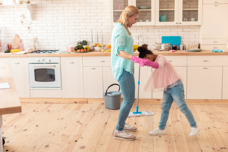 Jeans and sneakers. Cheerful mother and daughter wearing jeans and sneakers cleaning flat at the weekend