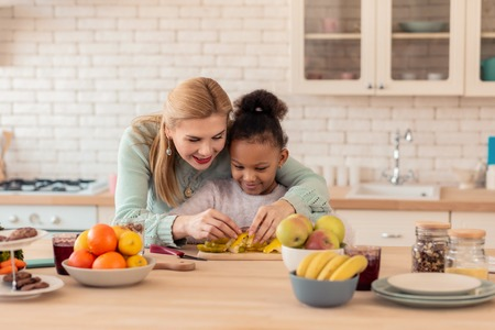 Enjoying cooking. Curly African-American daughter feeling happy enjoying cooking with her foster mom