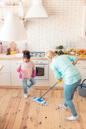 Girl helping. Cute little girl wearing jeans and pink shirt helping mom with cleaning the kitchen