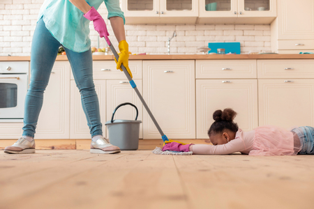 Lying on floor. Funny curly girl wearing pink blouse lying on the floor while mother mopping the floor