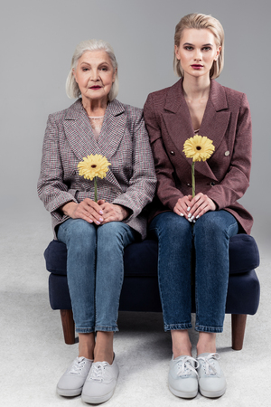 Posing during photoshoot. Precious good-looking tidy women sitting on little sofa close to each other and carrying yellow flowers Zdjęcie Seryjne