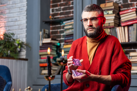 Red cardigan. Bearded handsome fortune-teller wearing red cardigan holding purple predicting cards