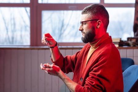 Glasses and bracelet. Bearded mature inspired diviner wearing glasses and bracelet reading  cards Reklamní fotografie