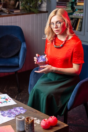 In red blouse. Blonde-haired diviner wearing long skirt and red blouse sitting in armchair and reading cards 版權商用圖片