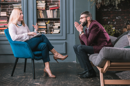 Sharing problems. Bearded businessman wearing suit and glasses feeling worried sharing problems with psychologist Reklamní fotografie