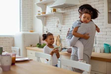 Need your help. Positive delighted child standing near her mother and holding her bowl with breakfast Stock Photo