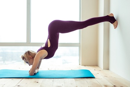 Hands on mat. Skinny strong woman showing her sportive skills while using mat as base for unusual posture