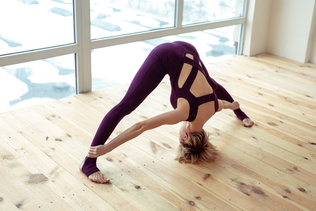 Widely disposing legs. Short-haired lady being in good shape and doing yoga on ordinary wooden floor