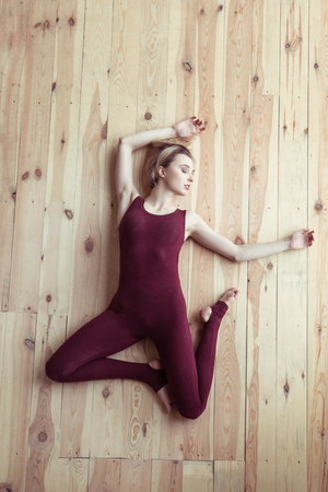 On wooden floor. Beautiful young lady with closed eyes lying in tragic posture while wearing red outfit