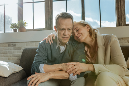 Hugging each other. Pleasant smiling woman supporting her short-haired husband while they saving their relationships Banco de Imagens