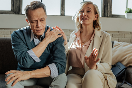 Upset man. Expressive blonde wife in light outfit calming her husband down while they discussing crises with therapist
