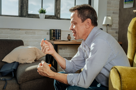 Short-haired man resting. Confused old man in striped shirt looking on blue capsule during every day routine Stock Photo