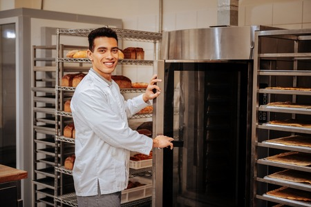 Standing near oven. Pleasant beaming dark-haired baker standing near big oven in the kitchen