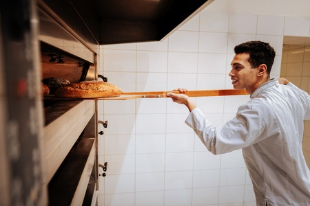 Taking baguettes. Dark-haired talented baker smiling while taking baguettes out of oven