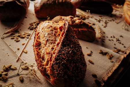 Topped with seeds. Close up of delicious rye gluten free bread topped with seeds lying on table Archivio Fotografico