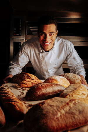 Table with bread. Cheerful dark-eyed young baker smiling broadly standing near table with bread