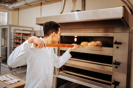Bread ready. Young skillful baker wearing white uniform taking ready bread out of big oven in the kitchen Stock Photo