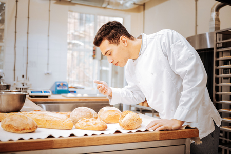 Just baked bread. Dark-haired baker wearing white jacket feeling satisfied while smelling just baked bread