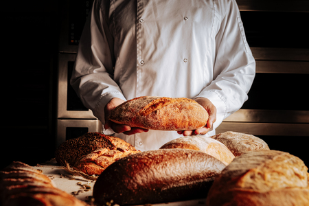 Presenting bread. Baker wearing white jacket presenting different wheat and rye gluten free bread Archivio Fotografico