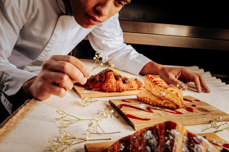 Baker decorating. Professional inspired baker decorating wooden plates with yummy desserts Standard-Bild