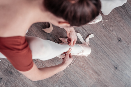 My outfit. Top view of a professional ballerina looking at her dancing shoes while putting them on Stock Photo