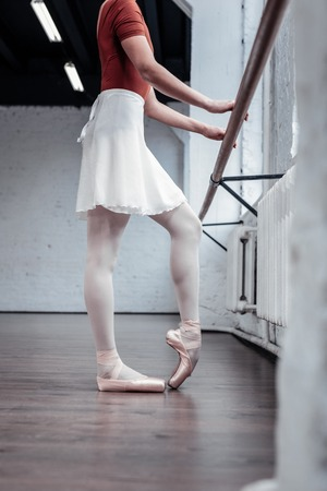 Professional occupation . Nice young ballerina standing near the barre while practicing her dancing movements