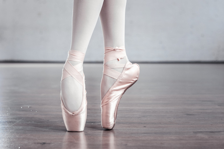 On tiptoes. Close up of female legs standing on tiptoes in ballet shoes Zdjęcie Seryjne