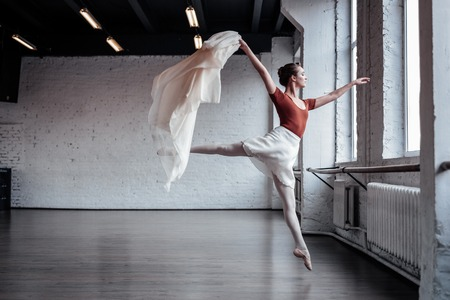 Beauty and grace. Attractive slim ballet dancer showing her grace while jumping during the dance Stockfoto