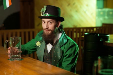 Nice day. Dark-haired bearded young man wearing a leprechaun costume looking pleased