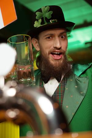 Wonderful mood. Dark-haired bearded young man wearing a leprechaun costume feeling wonderful