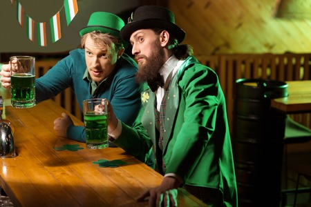 Something interesting. Fair-haired young man wearing a green hat and his bearded friend looking attracted Stock Photo