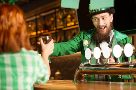 Lets have a drink. Dark-haired bearded young man in a leprechaun hat drinking with his friends while standing at the bar counter Standard-Bild