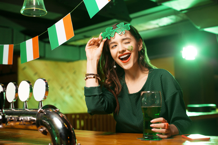 Winking girl. Long-haired young cute girl in a nice green blouse winking while sitting at the bar counter