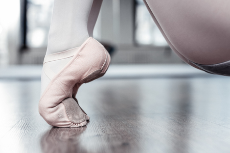 Professional dancer. Close up of female feet standing on toes while wearing special shoes