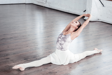Beautiful movement. Beautiful graceful ballet dancer leaning backwards with her hand up while doing the splits