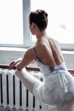 So beautiful. Pleasant nice ballet dancer looking into the window while practicing in the dancing hall Imagens