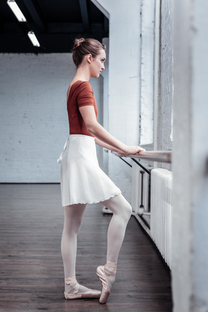 Constant practice. Pleasant nice woman standing at the barre while practicing her ballet movements Stock Photo
