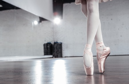 So slim. Close up of beautiful slim dancers legs standing on pointe shoes