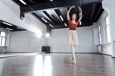 Skilled ballet dancer. Beautiful young woman holding her hands up while standing on pointe shoes