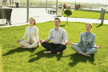 Yoga pose. Lucky sportive women and man sitting in yoga pose while enjoying their rest Stock fotó