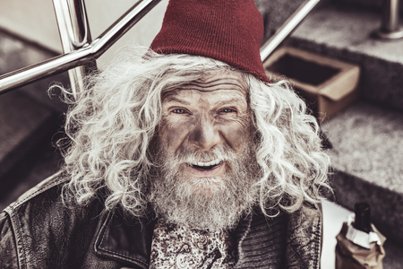 Sincere face. Portrait of old unwashed vagrant looking in the camera with wrinkles on forehead and open mouth. Imagens