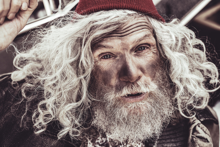 Hi there. Close up portrait of elderly almsman in red beanie whose greeting the passerby.
