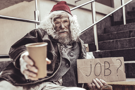 Step right up. Homeless elderly holding cup and trying to draw attention to himself. Stock Photo