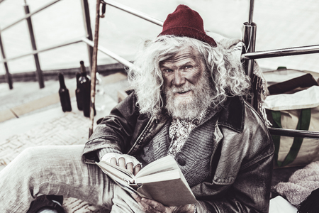 Talking with stranger. Untidy mendicant retelling the plot of the interesting book to the passerby while reading. Stock Photo