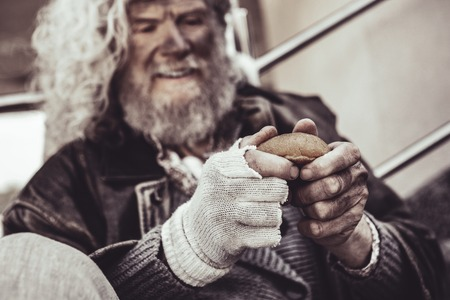Breakfast for homeless. Smiling Caucasian homeless man sitting and happy to get a bun and holding it with both hands.