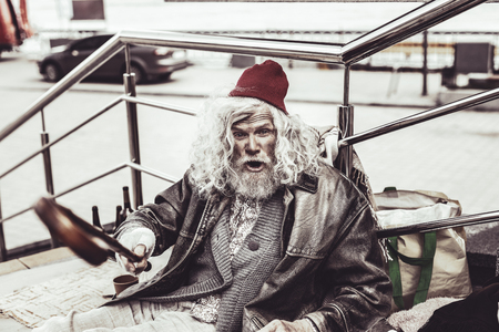 Serious menace. Angry old almsman sitting near railing and threatening strangers with wooden cane.