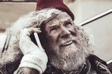 Private conversation. Portrait of homeless Caucasian man talking on smartphone and inspiredly looking at the sky.