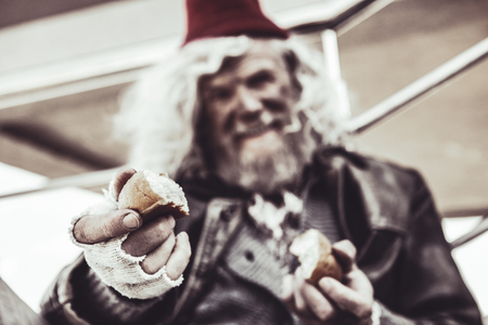 Take one. Blurred close up of old smiling almsman whos holding pieces of baking and sincerely sharing it with photographer. Stok Fotoğraf